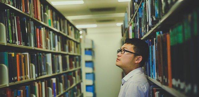 本棚を見上げる眼鏡の青年