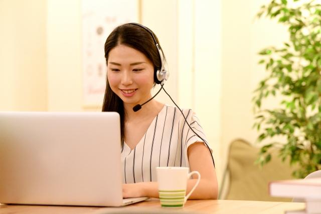 ヘッドセットを付けてパソコンに向かう女性