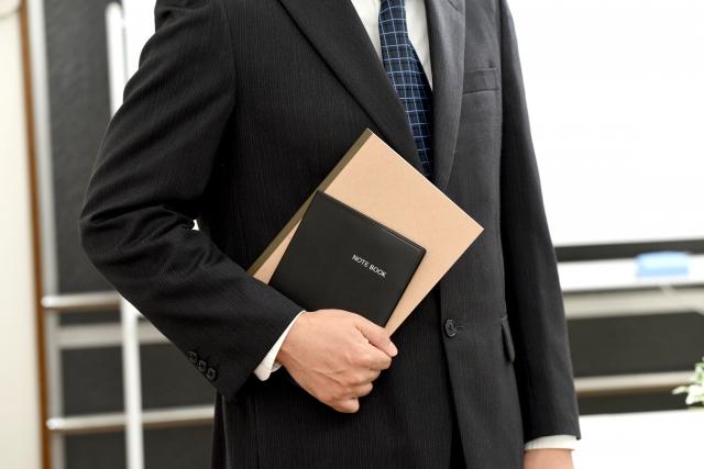ノートと手帳を持つビジネスマン