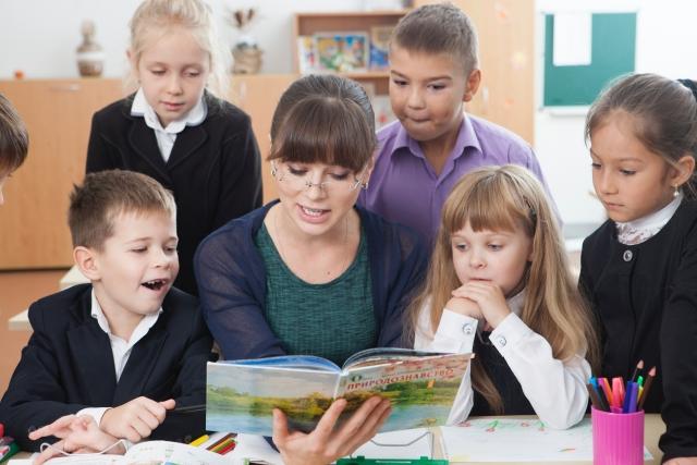 先生の周りに集まる小学生