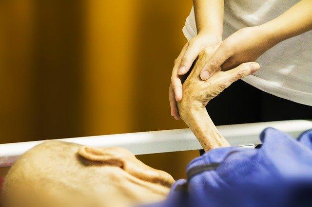寝たきり老人の手を握る看護師