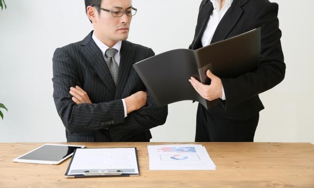 厳しい顔で書類を見つめるスーツの男性